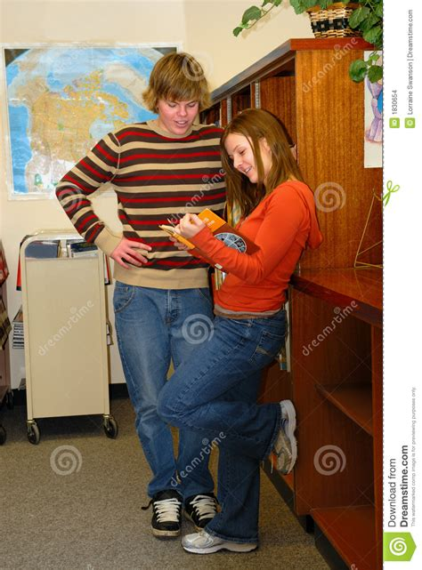 Teens flirting in Library stock photo